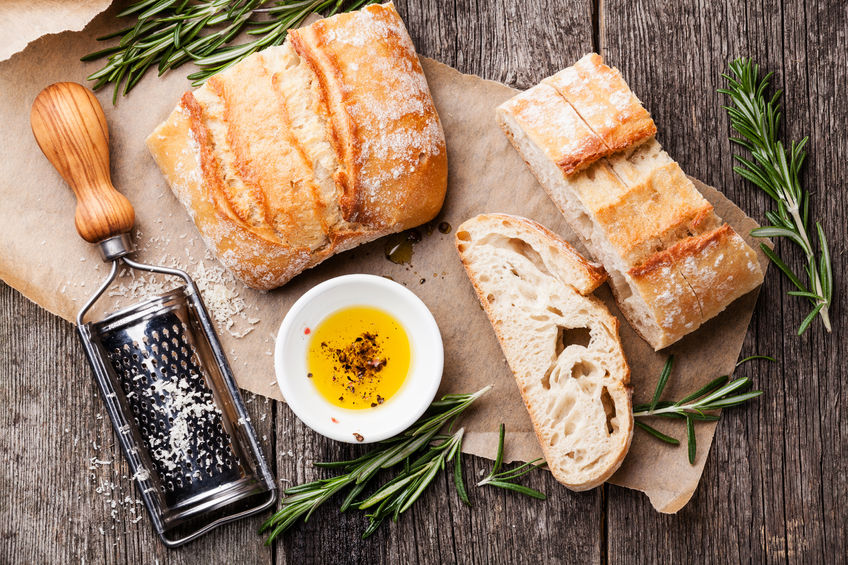 osteoporosis and gluten sensitivity - sliced bread ciabatta and extra virgin olive oil on wooden background