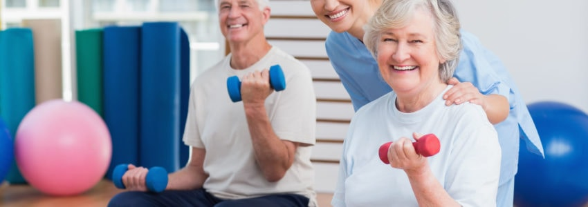 Senior couple in gym doing weight bearing exercise