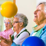 Senior Women Exercising While Sitting With Ball