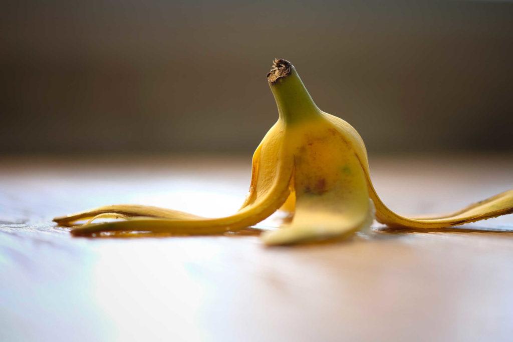 Banana peel fell on the wooden floor.
