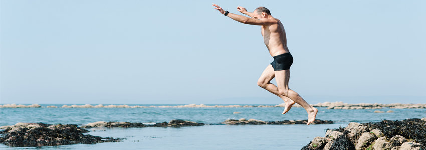 Senior male jumping into beach water