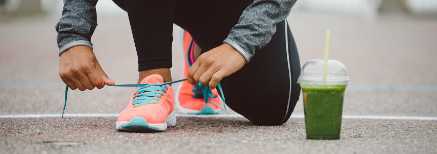 Runner tying shoes with green smoothie