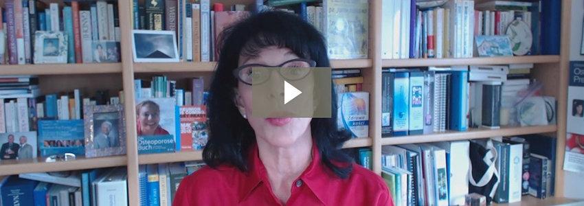 Lara Pizzorno in red shirt in front of bookshelf