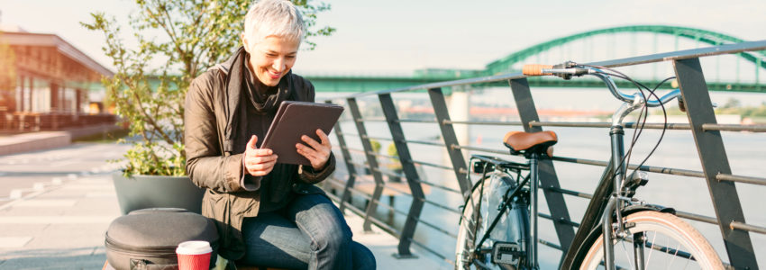 Mature woman riding her city bicycle to and from work. She is commuting to work in the morning by riverside. Making break, sitting on the bench by the fence, drinking coffee and using digital tablet. On bench beside her is backpack and coffee.