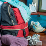 Backpack, camera, and shoes next to bed