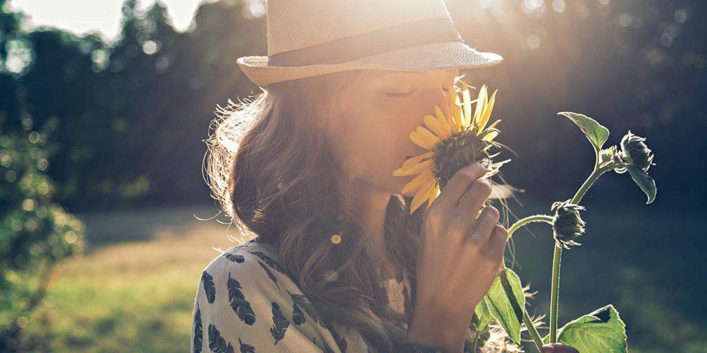A menina sente o cheiro de girassol ao sol - vitamina D