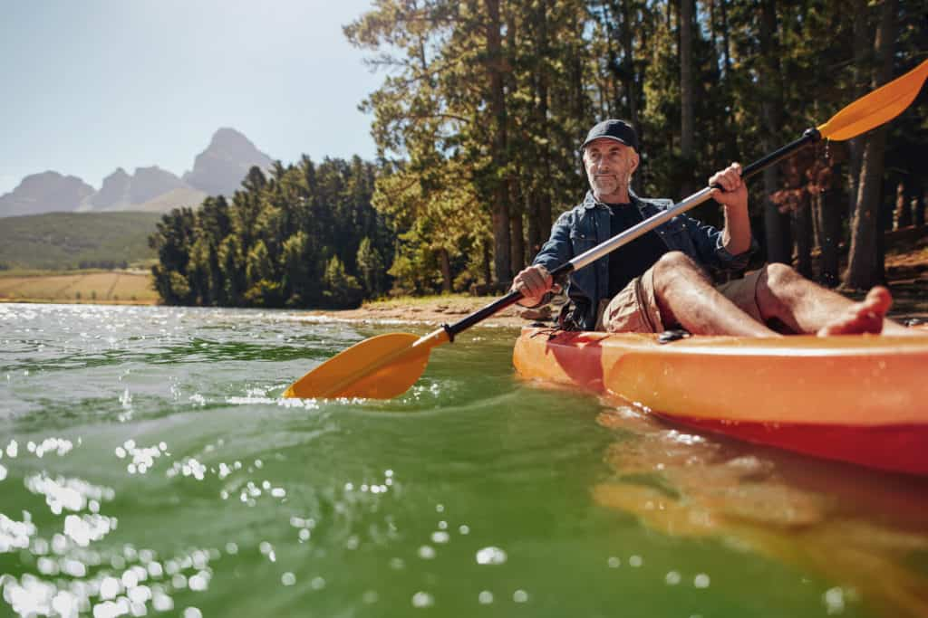 Portrait of a mature man with enjoying kayaking in a lake.