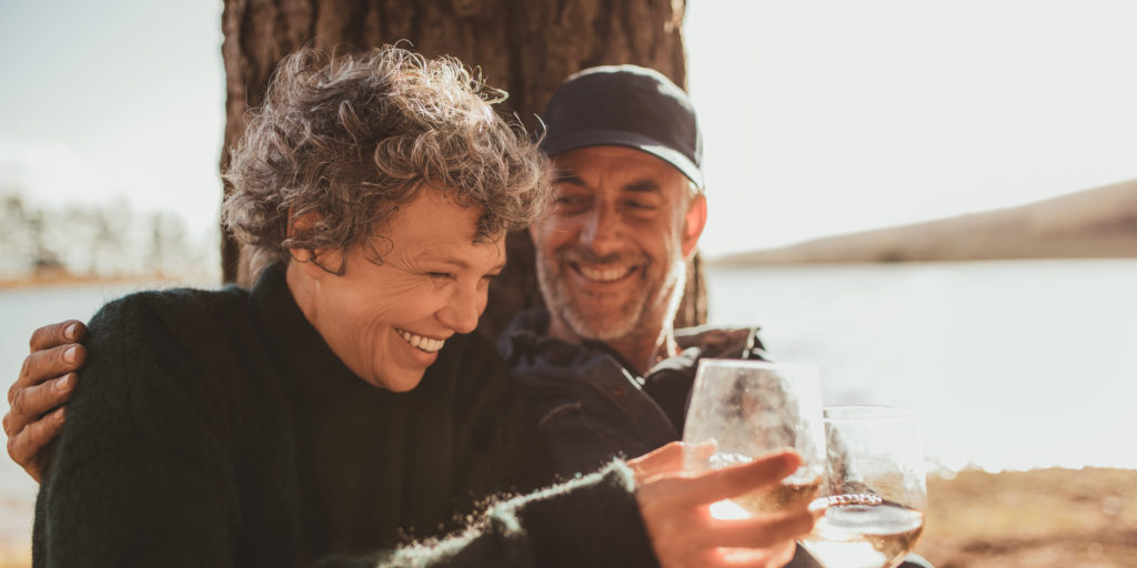 Portrait of relaxed mature couple having a glass of wine at campsite. Senior man and woman toasting wine at on summer day. Optimistic