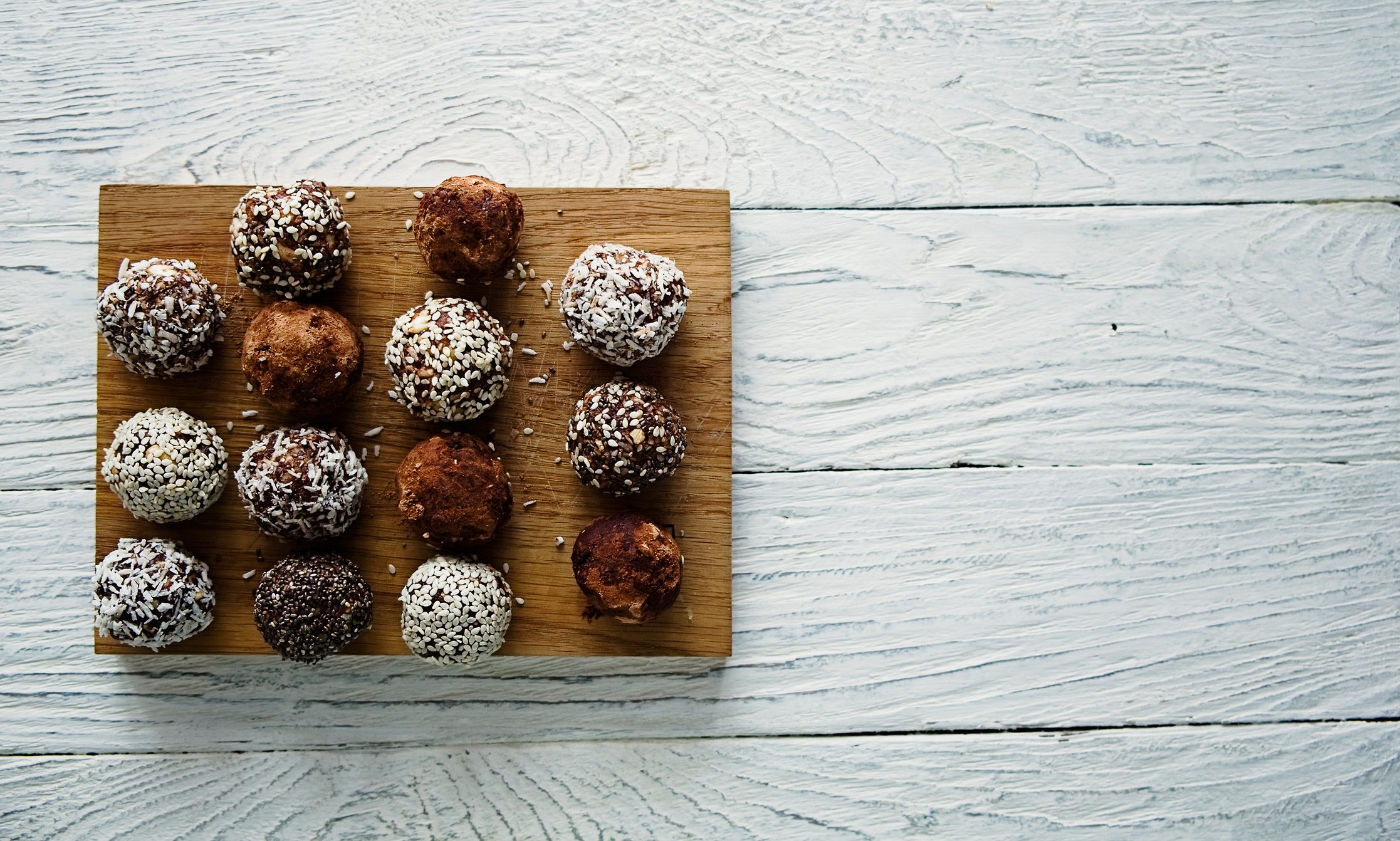 Healthy raw energy balls on a white wooden background