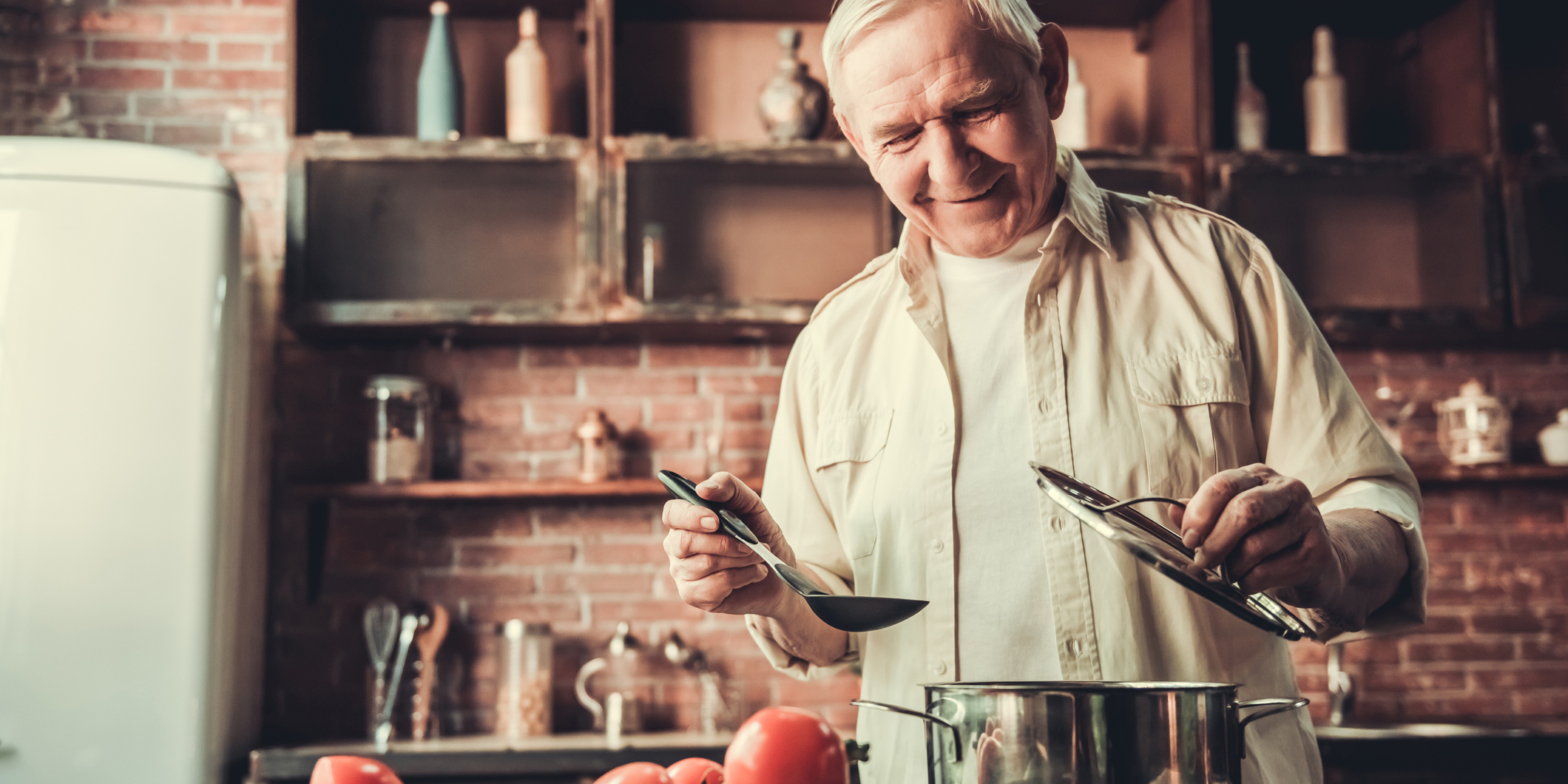 Handsome senior man is smiling while cooking in kitchen