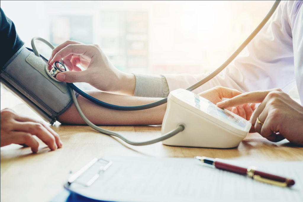 Doctor Measuring blood pressure - blood pressure meds are drugs that cause osteoporosis
