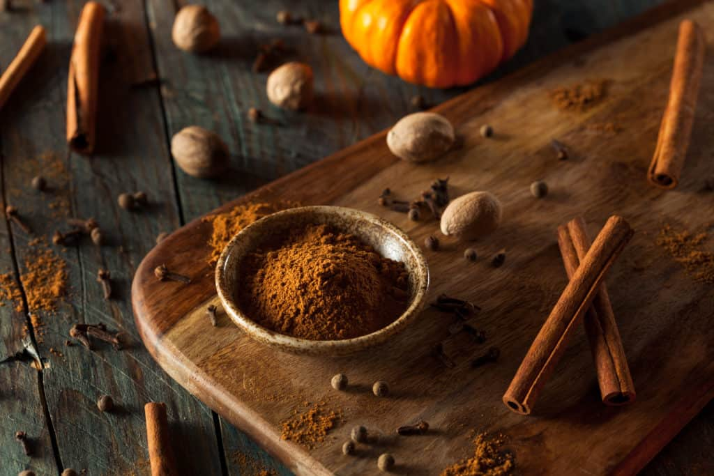 pumpkin pie spices on a darkwood table