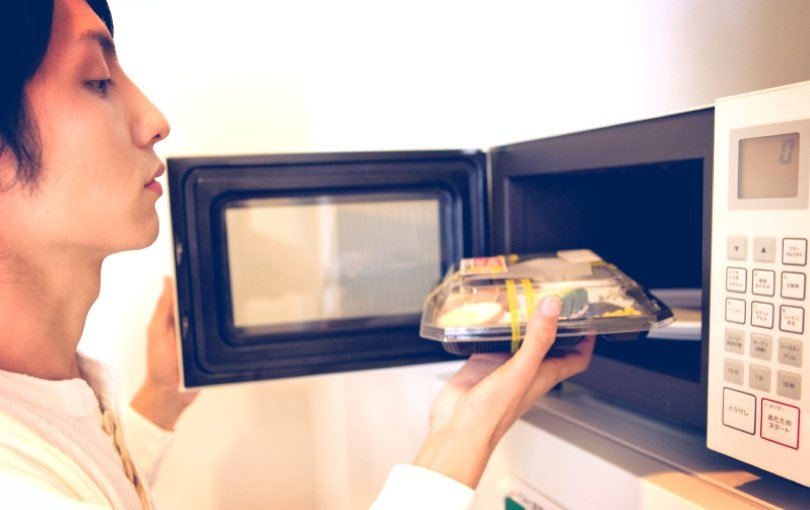 Man putting boxed lunch into microwave