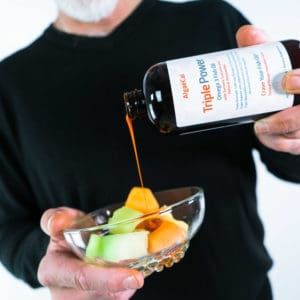 A person pouring Triple Power Fish Oil