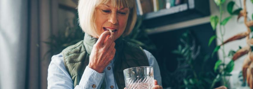 Woman taking an AlgaeCal Plus calcium supplement